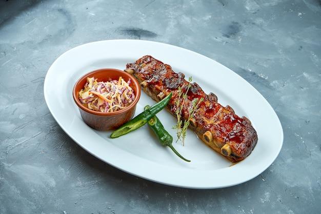 Порционные запеченные свиные ребрышки bbq с салатом cole slow и острым перцем в белой тарелке
