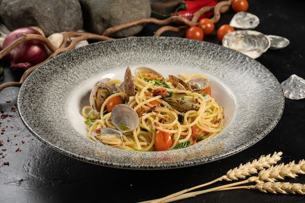 A portion of boiled spaghetti pasta with seafood, mussels and vegetables