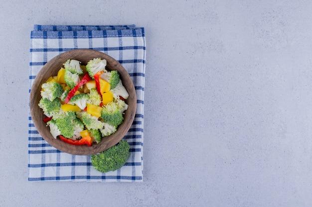 Porzione di insalata di broccoli e peperoni in una ciotola su un asciugamano piegato su fondo marmo. foto di alta qualità