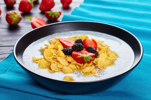 A portion of chia seeds with milk and corn flakes topped with fresh strawberries