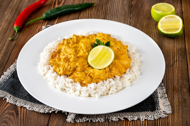 Portion of chicken curry garnished with rice and fresh lime