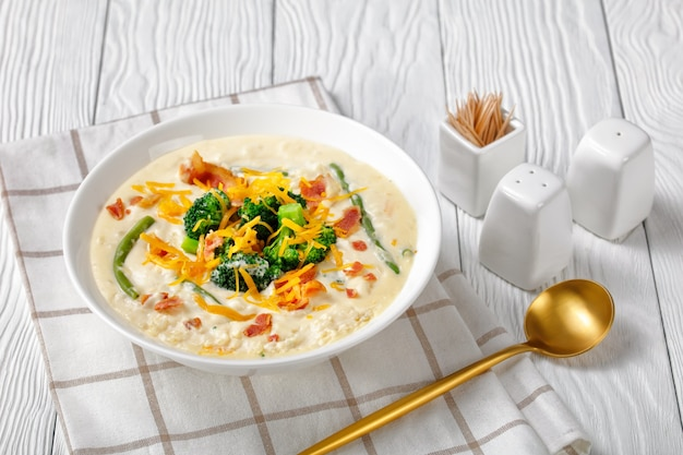 Portion of cream soup with broccoli, green bean, fried bacon, and shredded cheddar cheese in a white bowl on a wooden table