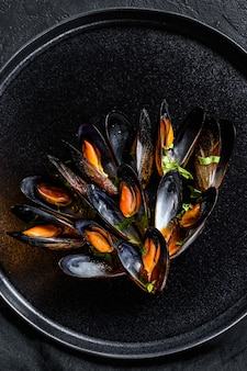Portion of delicious mussels in tomato sauce and parsley. black background. top view