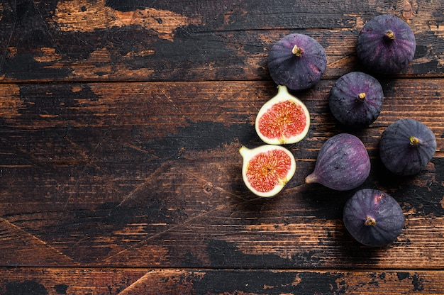 Portion of fresh figs on vintage wooden table. dark wooden background. top view.