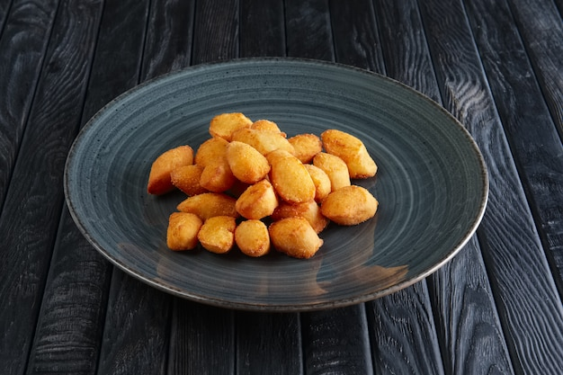 Portion of fried potato balls on dark wooden table