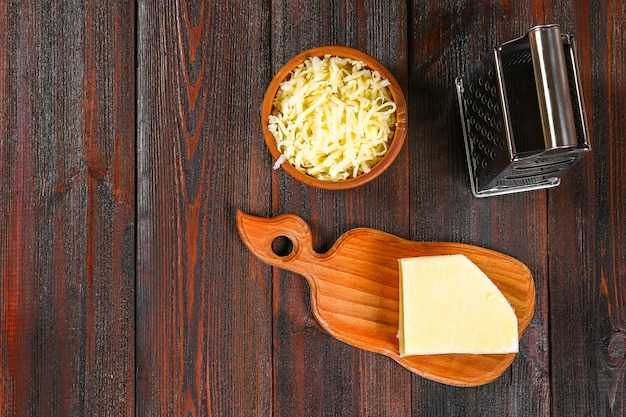 Portion of grated cheddar cheese on rustic wooden table.