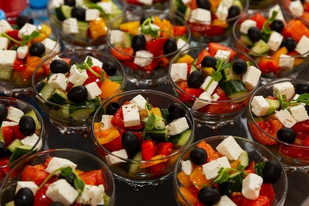 Порционный греческий салат на столе. организация мероприятий, торжеств и деловых встреч.