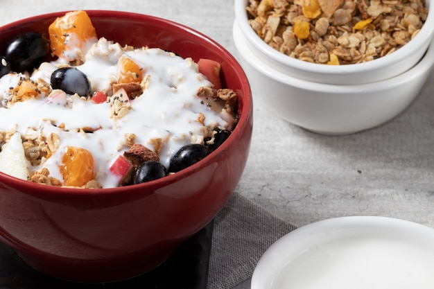 Portion of healthy fruits salad covered with granola, quinoa and yogurt in a red bowl.