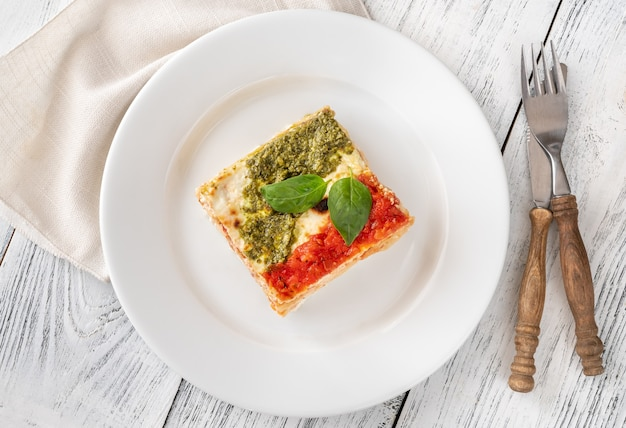 Portion of lasagne topped with tomato sauce and pesto