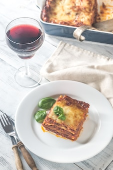 Portion of lasagne with a glass of wine