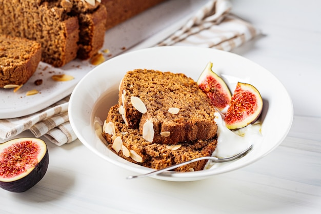 Portion of nut-fruit bread with yogurt and figs. vegan banana bread, white background.