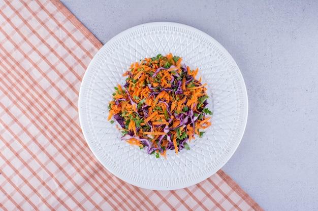 대리석 배경에 양배추와 당근 샐러드의 일부입니다. 고품질 사진