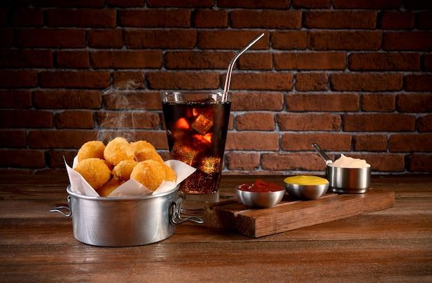 マヨネーズ、ケチャップ、マスタード、ソーダを添えたチーズボール(タラまたはビーフ)の一部