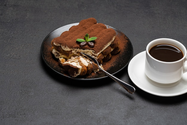 古典的なティラミスデザートとコンクリートの背景やテーブルに新鮮なエスプレッソコーヒーのカップの部分