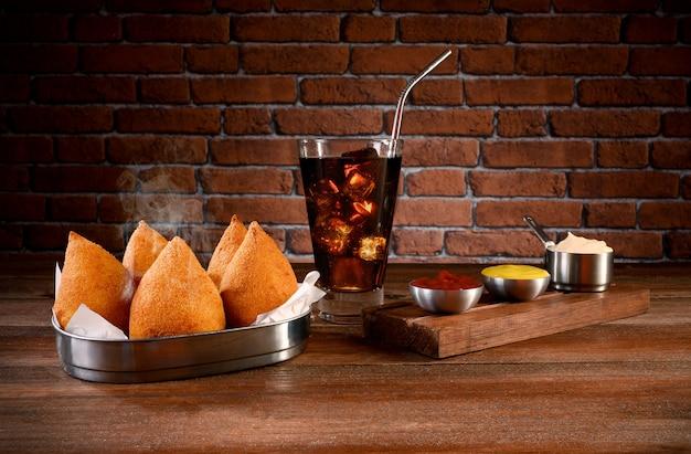 Порция коксиньи - традиционная бразильская еда с кетчупом, майонезом, горчицей и содовой