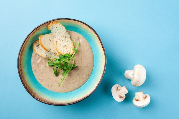 Порция сливочного пюре-пюре супа с шампиньонами, сметаной, зеленью, гренками в деревенской миске на синем фоне