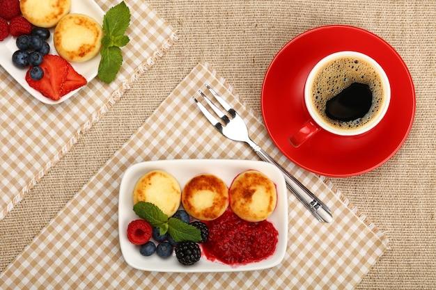 Порция сырных блинчиков европейского десерта с фруктами и чашкой черного кофе