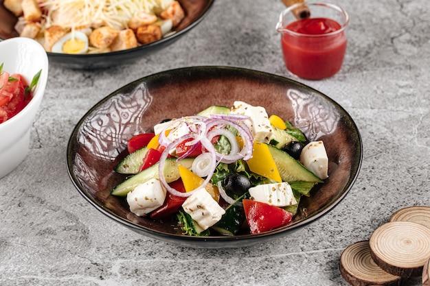 Порция свежего греческого салата на сером фоне