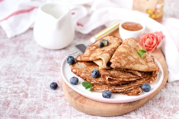 はちみつとブルーベリーの揚げパンケーキの一部、皿、木の板、テーブル。