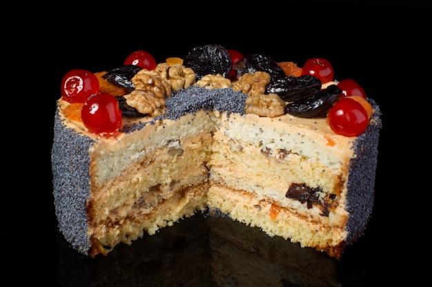 黒の背景にケシの実をまぶしたフルーツケーキクルミの部分