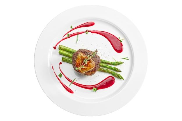 Порция стейка миньон на гриле с фуа-гра и спаржей, ягодным соусом в белой тарелке. изолированный на белой поверхности. вид сверху