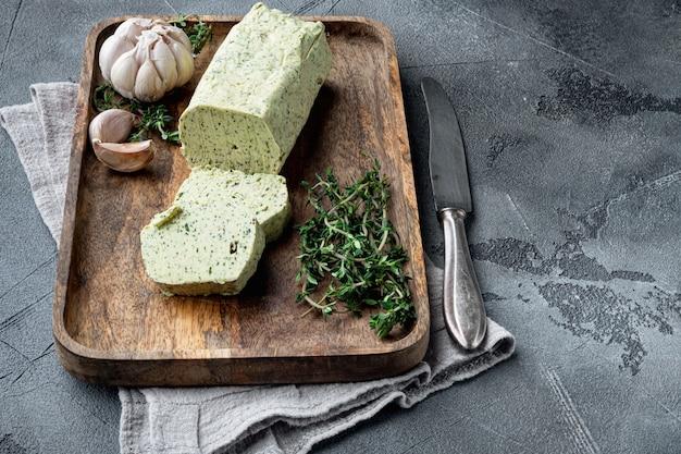 Часть масла из трав с чесноком, базиликом, орегано, петрушкой, на сером каменном столе
