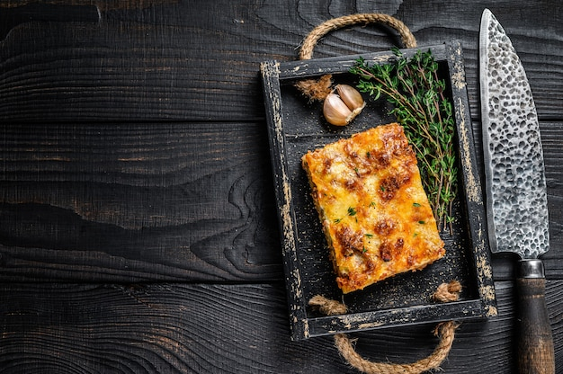 나무 쟁반에 다진 쇠고기 고기와 토마토 볼로네제 소스를 곁들인 라자냐 부분. 검은 나무 배경. 평면도. 공간을 복사합니다.
