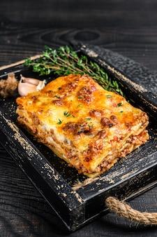 나무 쟁반에 다진 쇠고기 고기와 토마토 볼로 네즈 소스를 곁들인 라자냐 부분