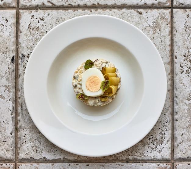 Порция салата оливье на белой тарелке, вид сверху