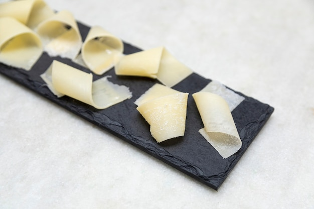 フレーク状のパルメザンチーズの一部と黒い石のバルサミコ酢