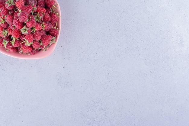 Часть малины в розовой миске на мраморном фоне. фото высокого качества