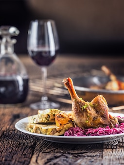 Часть жареной утиной ноги краснокочанной капусты домашних пельменей на тарелке и красное вино на заднем плане.