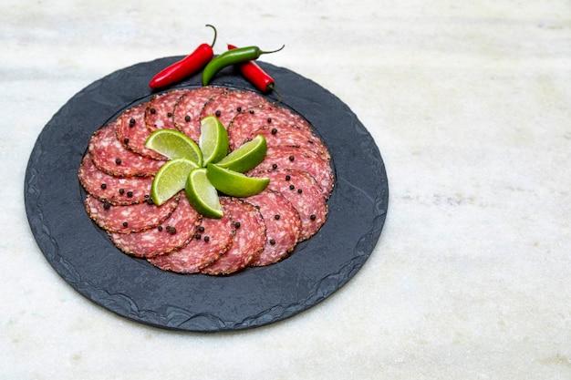 Часть салями на черной каменной тарелке
