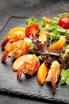 검은 접시에 새우와 야채 샐러드의 부분