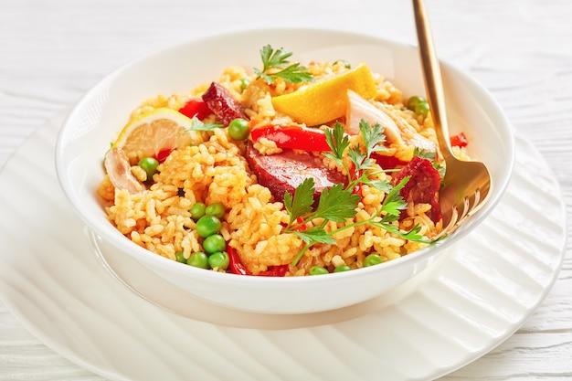 발렌시아 봄바 쌀, 닭 허벅지 고기, 초리 조 소시지, 야채 및 향신료와 함께 스페인 치킨 빠에야의 부분은 흰색 나무 테이블에 흰색 접시에 제공, 근접