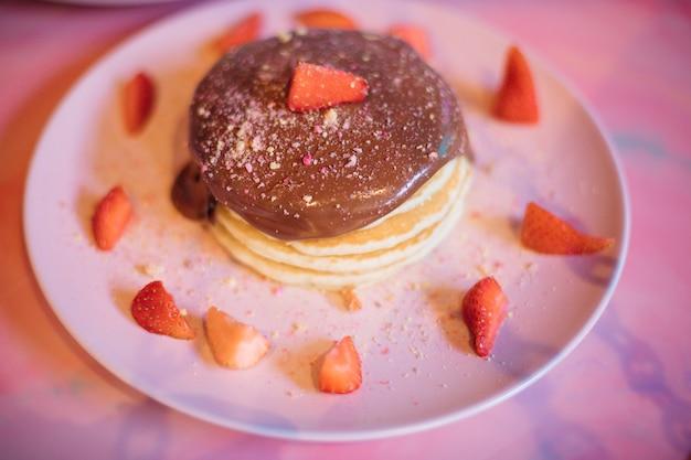 Часть сладких блинов с шоколадной начинкой и кусочками клубники на розовой тарелке.