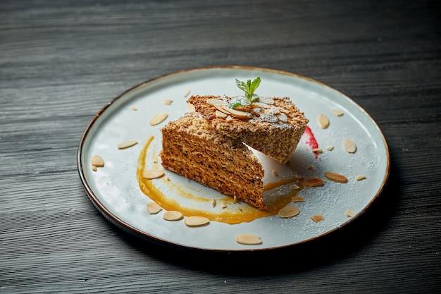 Порция сладкого вафельного торта со сгущенкой в белой тарелке на деревянном фоне