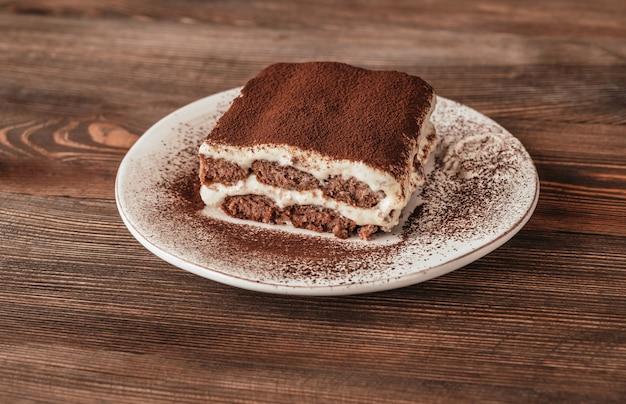 Часть итальянского десерта тирамису на деревянных фоне