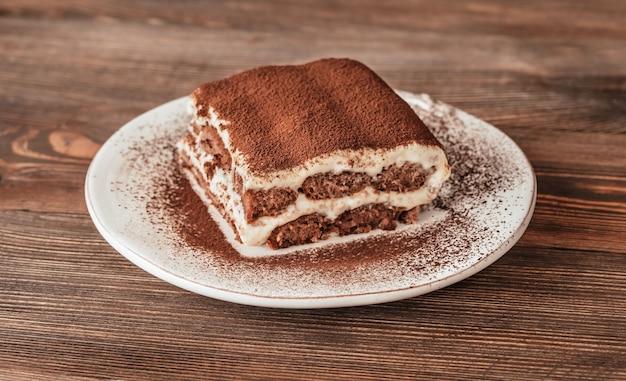 Часть итальянского десерта тирамису на деревянном столе