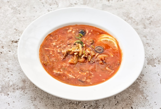 Порция томатного супа с колбасой и оливками в белой тарелке