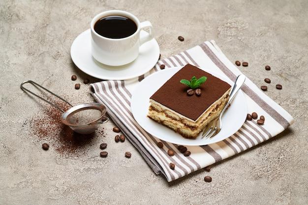 灰色のコンクリートのテーブルに伝統的なイタリアのティラミスデザートとコーヒーの一部