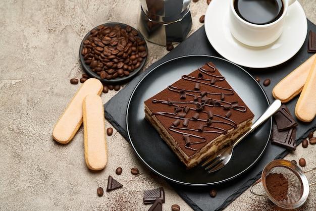 회색 콘크리트 테이블에 전통적인 이탈리아 티라미수 디저트와 모카 커피 메이커의 부분