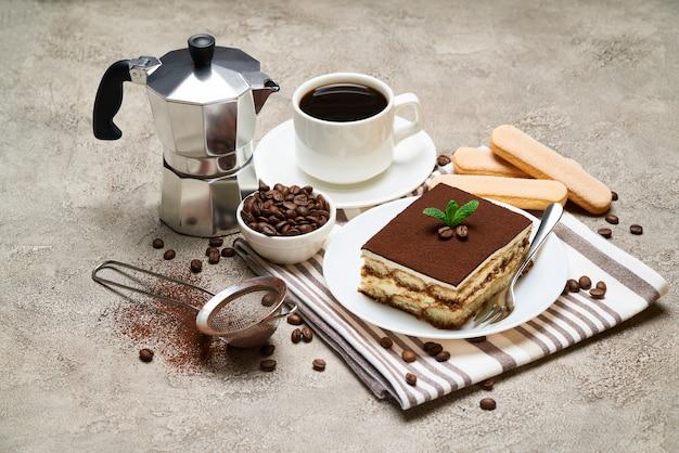 灰色のコンクリートのテーブルに伝統的なイタリアのティラミスデザートとサボイアルディクッキーの一部