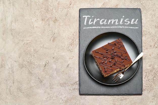 Часть традиционного итальянского десерта тирамису на каменной сервировочной доске с мелом рукописный текстовый знак