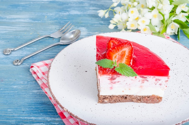 Portion piece of cottage cheese cheesecake with fresh strawberries and strawberry jelly