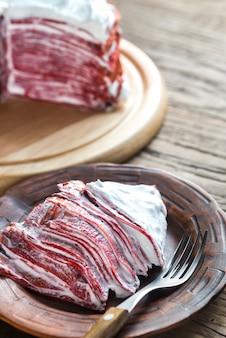 Portion of red velvet crepe cake on the wooden table