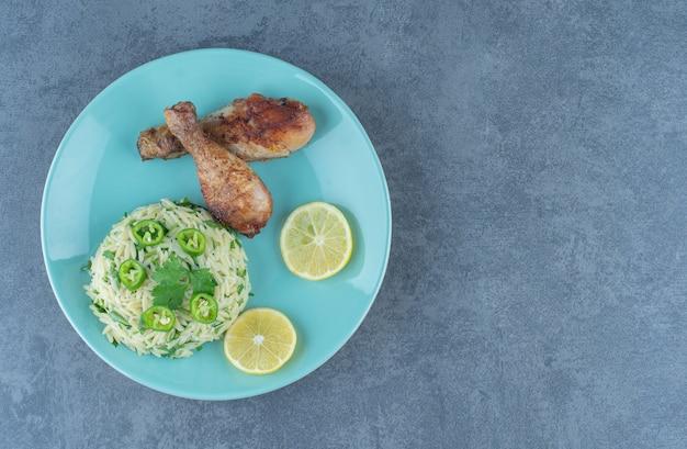 Porzione di riso con cosce di pollo sul piatto blu.