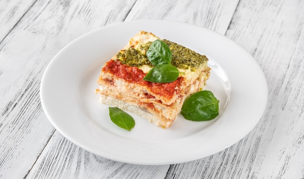 Portion of ricotta lasagne topped with tomato sauce and pesto