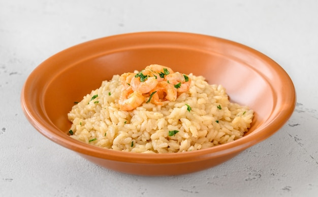 Portion of risotto garnished with prawn in the bowl