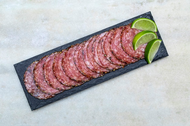 Portion of salami on black stone plate